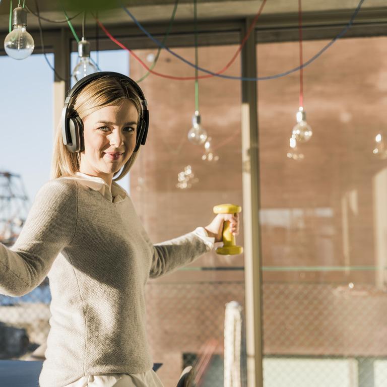 Frau mit Kopfhörer steht im Wohnzimmer und macht Übungen mit Hanteln in der Hand
