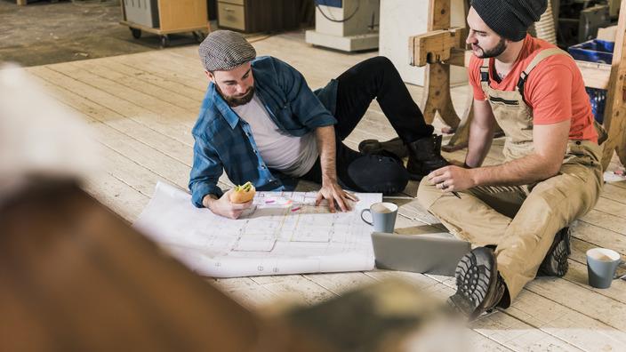 Zwei junge Männer, die auf dem Boden sitzen und sich gemeinsam einen Bauplan anschauen