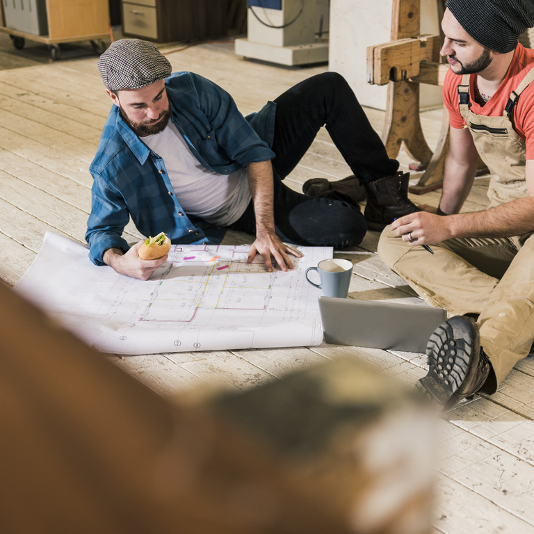 zwei Bauhandwerker liegen auf dem Boden und studieren einen Grundriss