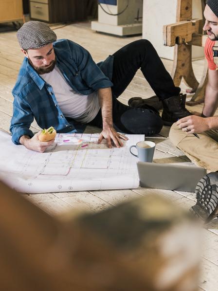 zwei Handwerker sitzen auf einer Baustelle auf dem Boden und besprechen einen Plan