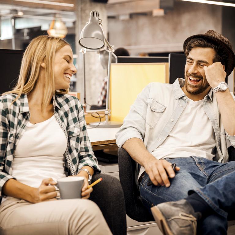 Frau und Mann lachen gemeinsam im Büro.