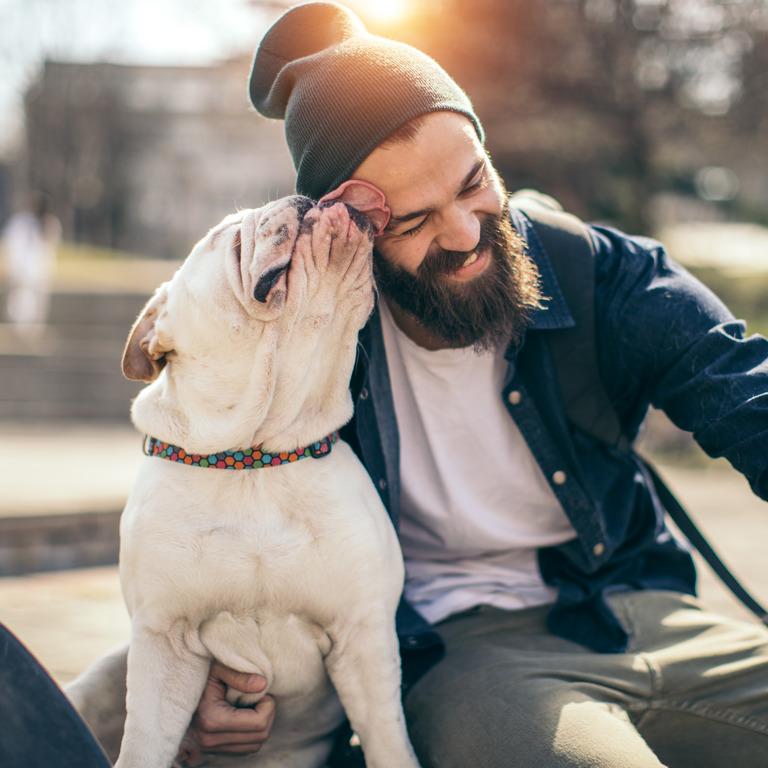 junger Mann sitzt mit seiner Bulldogge im Park