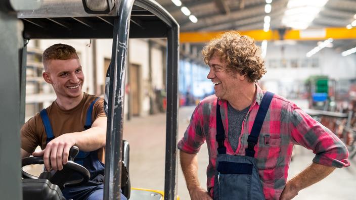 Zwei Arbeitskollegen unterhalten sich, der linke sitzt in einem Gabelstapler, der rechte steht daneben