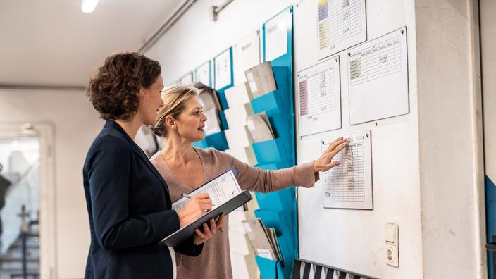 Zwei Frauen unterhalten sich im Büroflur über Pläne, die an der Wand hängen.