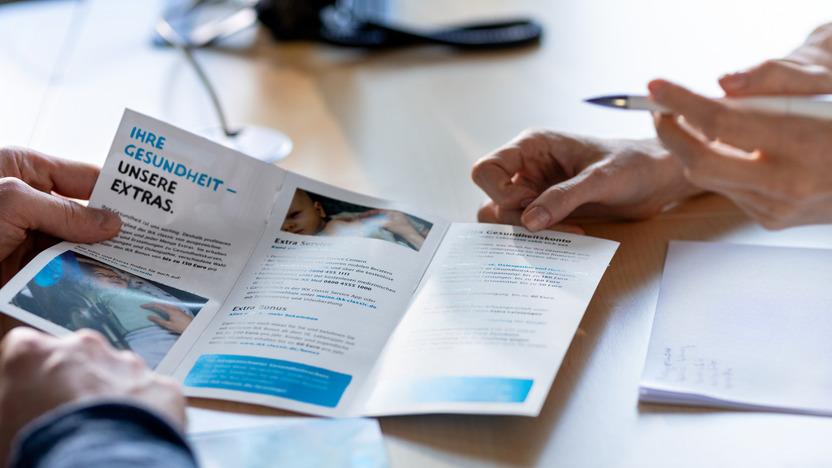 Händepaar zeigt auf einer Broschüre die Vorteile der IKK classic, ein weiteres Händepaar hält die Broschüre