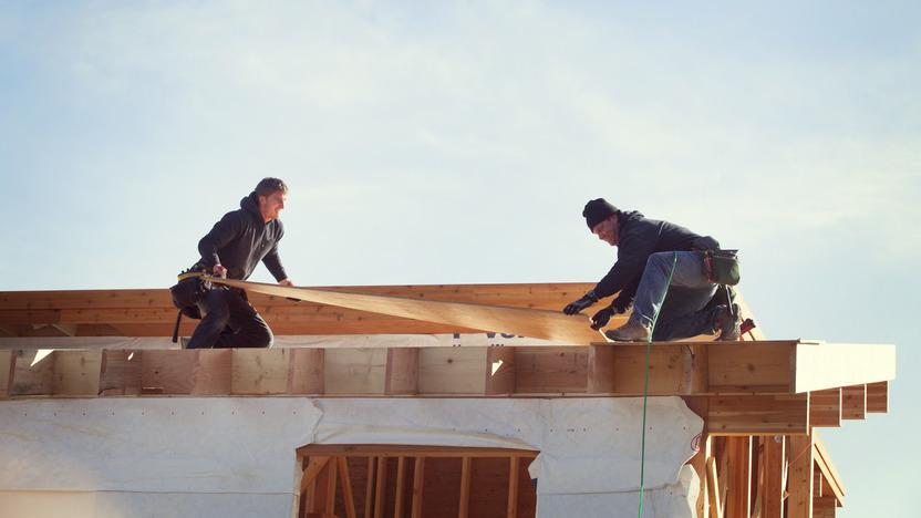 Zwei Handwerker arbeiten auf einem Hausdach und verlegen Holzplatten.