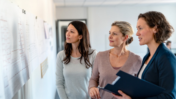 Chefin und zwei Mitarbeiterinnen schauen sich ein Chart zur Personalplanung an