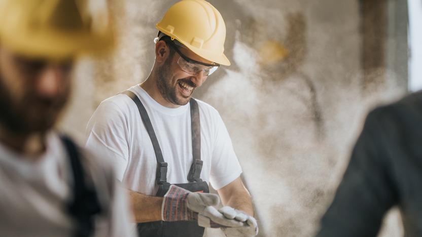 Bauarbeiter mit Helm zieht lachend seine Handschuhe aus.