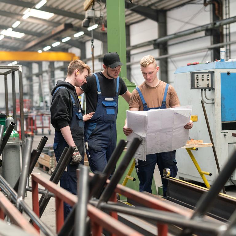 Junge Menschen stehen in einer Werkhalle und sprechen einen Plan durch.