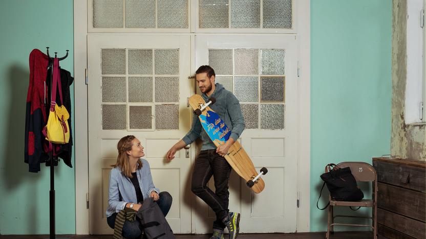 junges Paar lehnt an der Zimmertür einer Altbauwohnung, sie packt ihren Rucksack, er hält lässig ein Longboard im Arm