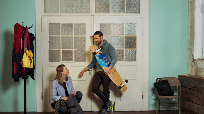 junges Paar lehnt vor einer Altbauzimmertür, sie packt ihren Rucksack, er hält ein Longboard im Arm