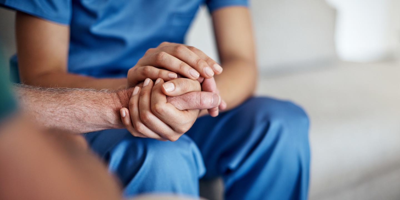 Pflegerin hält die Hand eines älteren Menschen