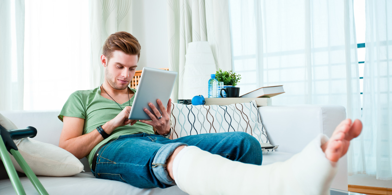 junger Mann sitzt mit einem eingegipsten Bein auf der Couch und bedient ein Tablet