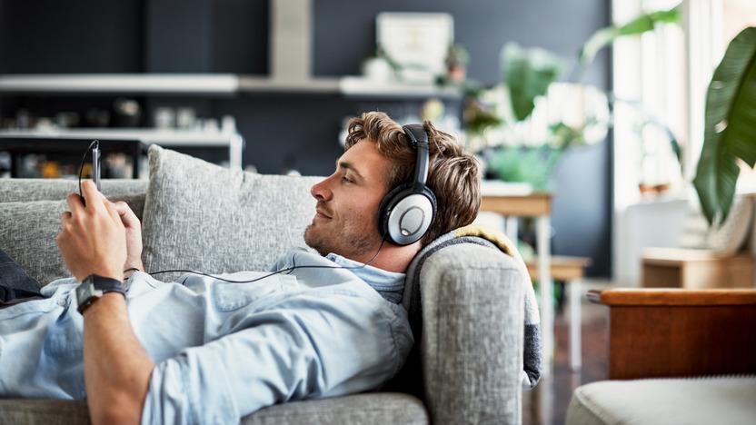 Junger Mann mit Kopfhörern liegt auf dem Sofa und schaut auf sein Handy