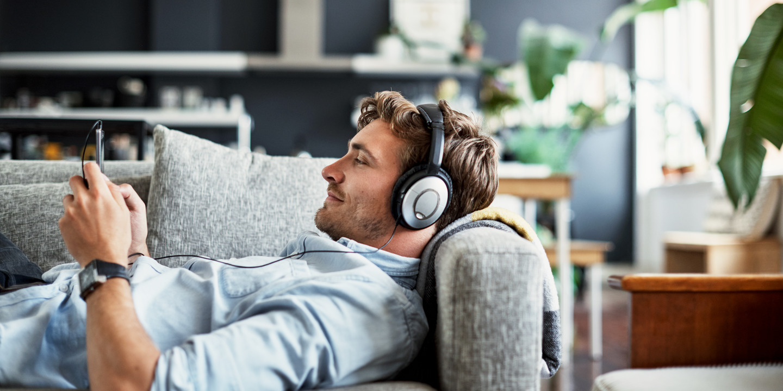 Junger Mann liegt mit Kopfhörern auf dem Sofa und bedient die Tinnitracks-App auf seinem Smartphone