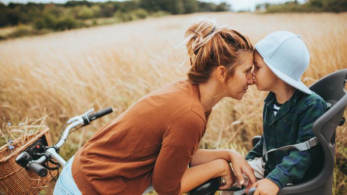 Mutter und ihr kleiner Sohn halten während einer Fahrradtourpause innig ihre Gesichter gegeneinander