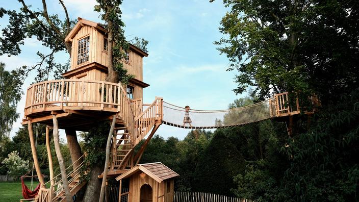 aufwändig gestaltetes Baumhaus aus Holz mit Hängebrücke