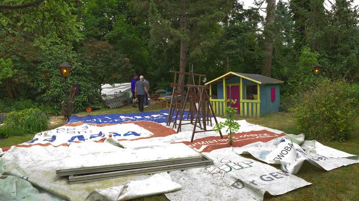 Material für das Baumhaus liegt ausgebreitet auf einer Plastikfolie auf dem Rasen