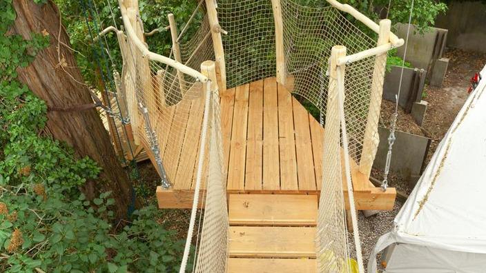 eine mit einem Netzgeländer gesicherte Treppe führt nach unten