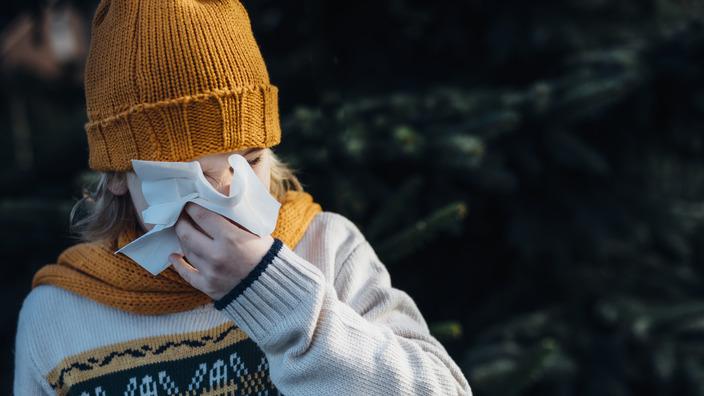 erkältetes Mädchen mit gelbem Schal und Strickmütze putzt sich die Nase mit einem Taschentuch