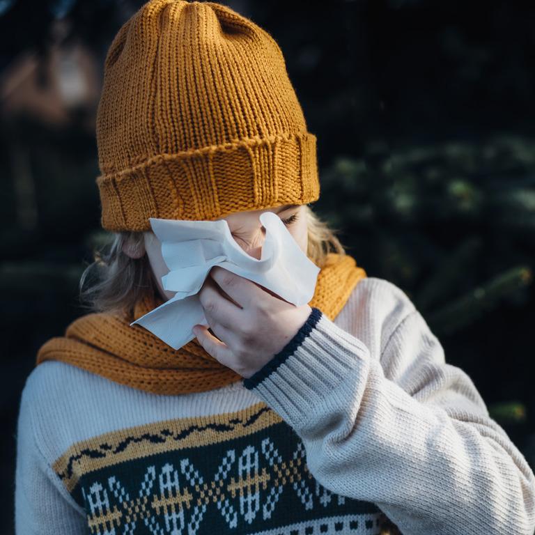 erkältetes Mädchen putzt sich die Nase mit einem Taschentuch
