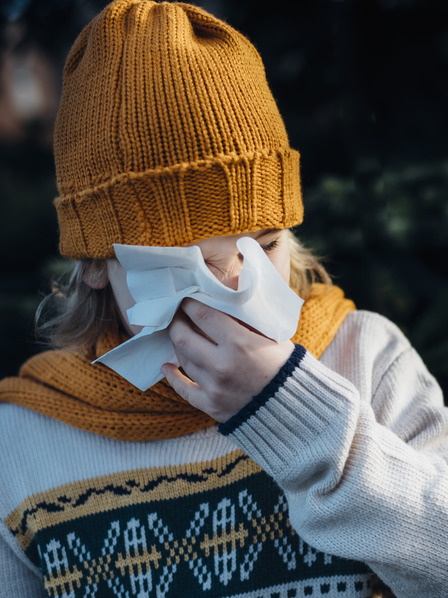 erkältetes Mädchen mit gelber Mütze und gelbem Schal putzt sich die Nase