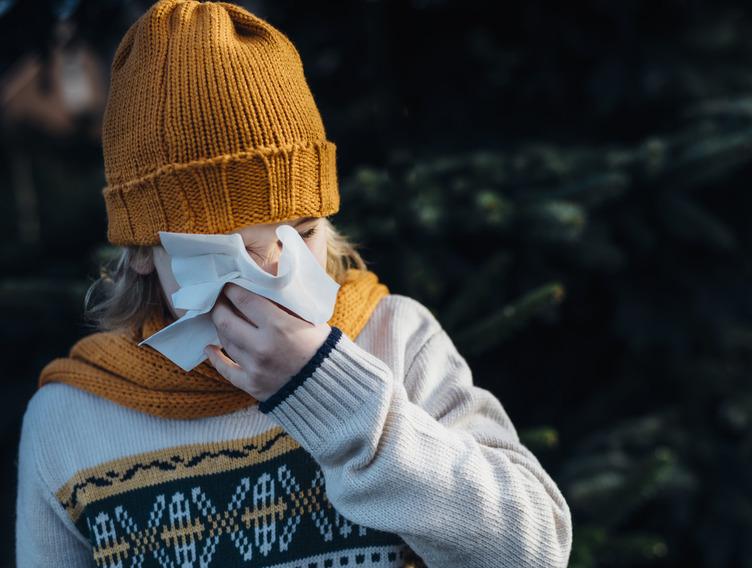 Person mit orangener Wollmütze und Strick-Pullover schnäuzt in ein Taschentuch.