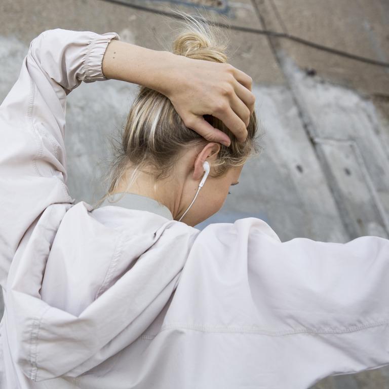 junge Frau mit In-Ear-Kopfhörern fasst sich gestresst an den Hinterkopf