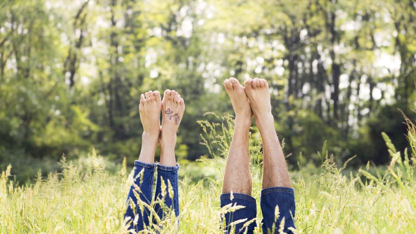 Mann und Frau liegen auf dem Rücken in einer Wiese und recken ihre nackten Füße in die Luft