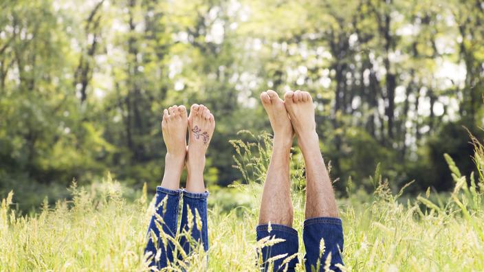 junges Paar liegt auf einer Wiese und streckt seine Füße in die Luft
