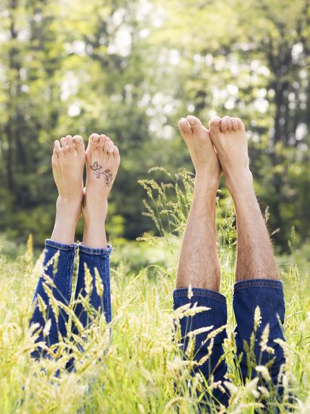Mann und Frau liegen mit dem Rücken auf einer Wiese und strecken ihre nackten Füße in die Luft