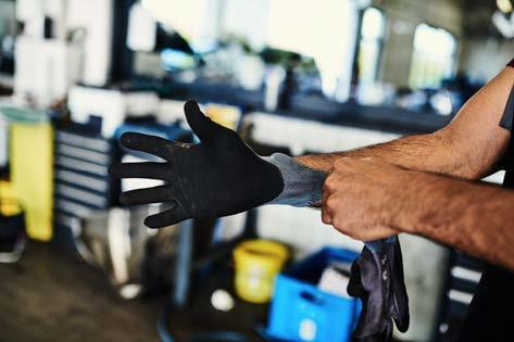 Hände eines Mannes, der gerade einen Handschuh anzieht
