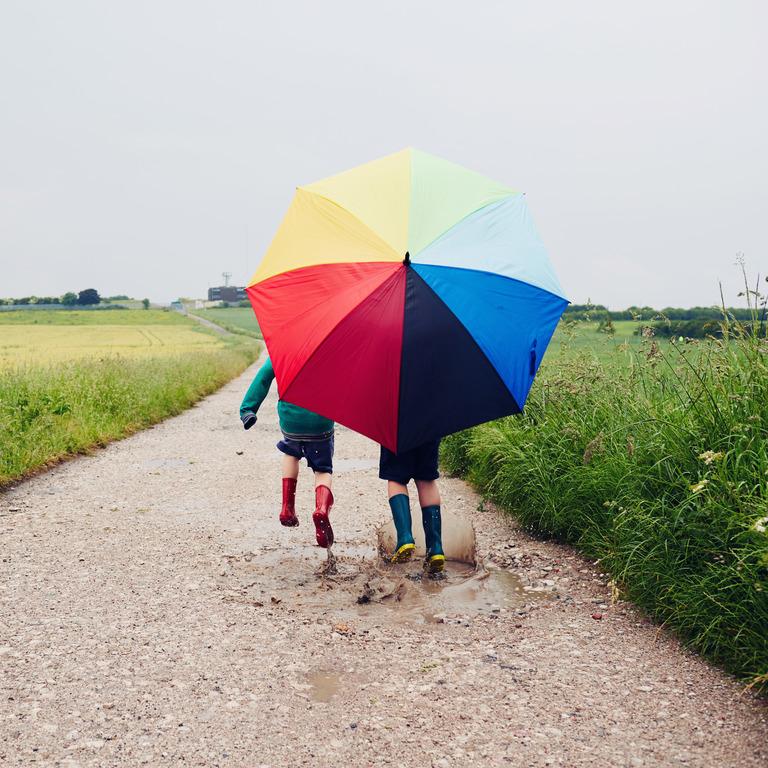 zwei Kinder in Gummistiefeln laufen mit einem großen regenbogenfarbenen Schirm über einen Feldweg im Regen