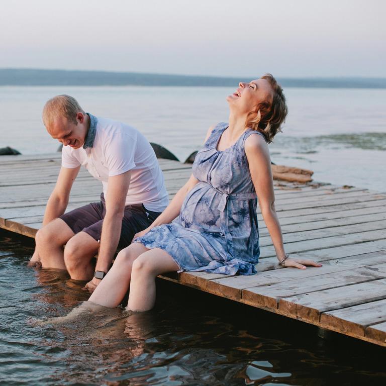 werdende Eltern sitzen entspannt auf einem Steg an einem See und lassen die Beine ins Wasser baumeln