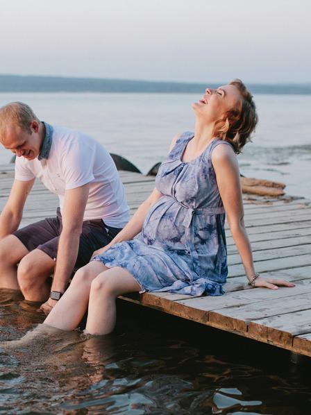 werdende Eltern sitzen entspannt auf einem Steg an einem See