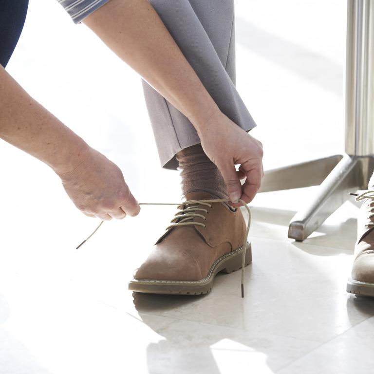 Frau schnürt einem älteren Mann die Schuhe zu