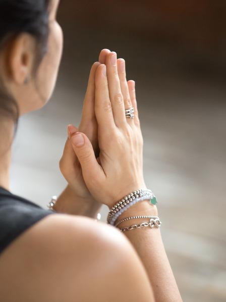 Frau meditiert und hält ihre Hände vor ihrer Brust