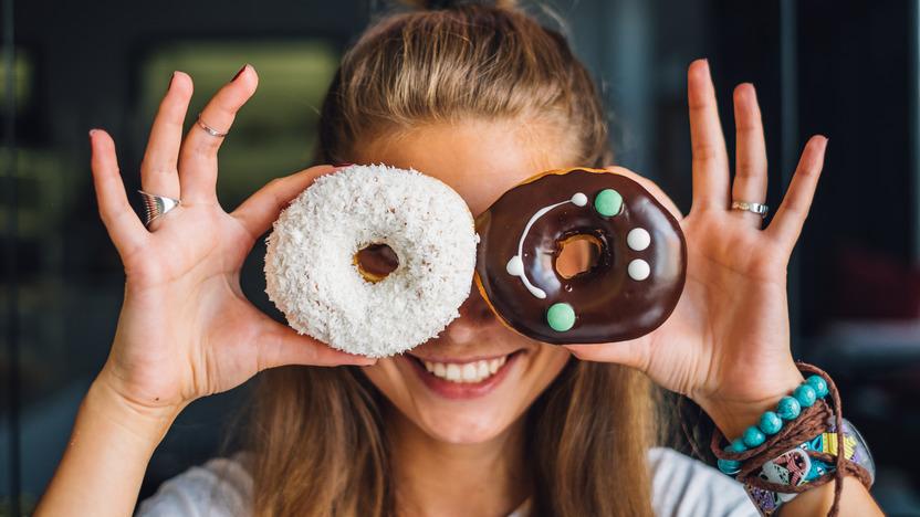 lächelnde junge Frau hält sich zwei bunt dekorierte Donuts vor die Augen
