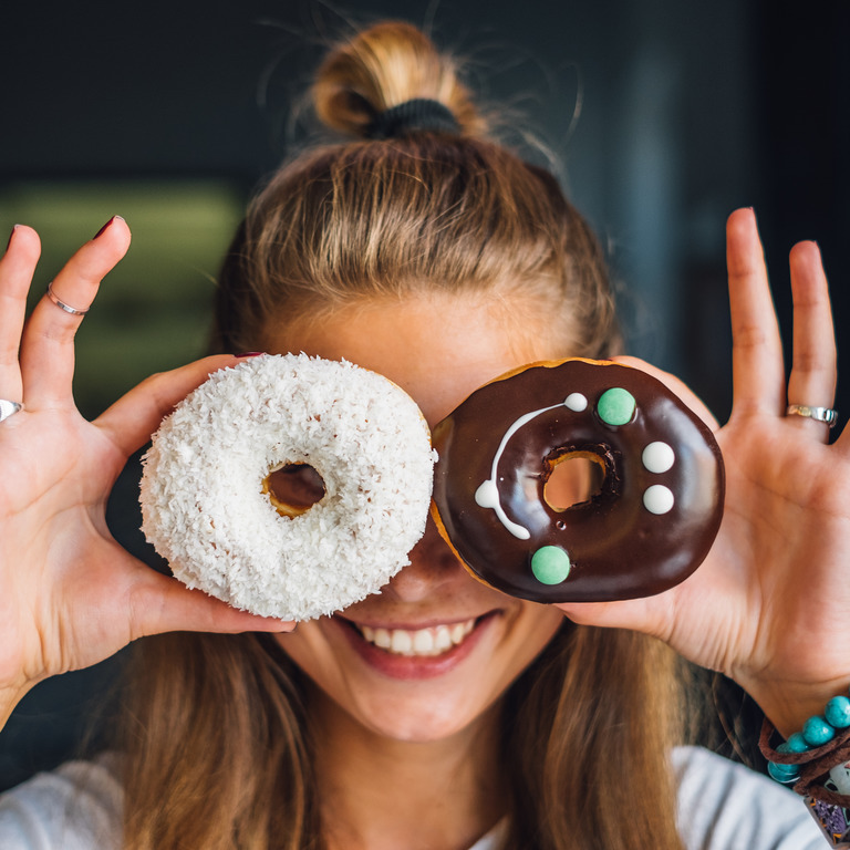 junge Frau schaut durch zwei Donuts