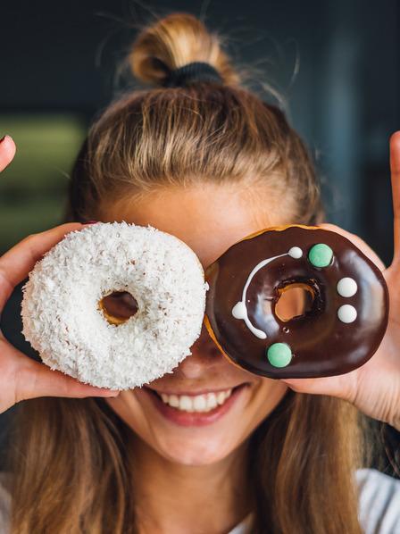 junge Frau schaut lachend durch zwei bunt dekorierte Donuts