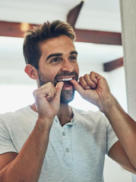 Mann pflegt seine Zähne mit Zahnseide