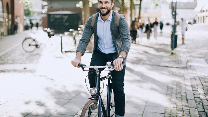 Mann mit Rucksack fährt mit dem Fahrrad durch die Stadt