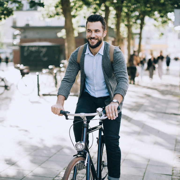 Der junge Man mit Bart fährt im Sommer mit dem Fahrrad zur Arbeit.