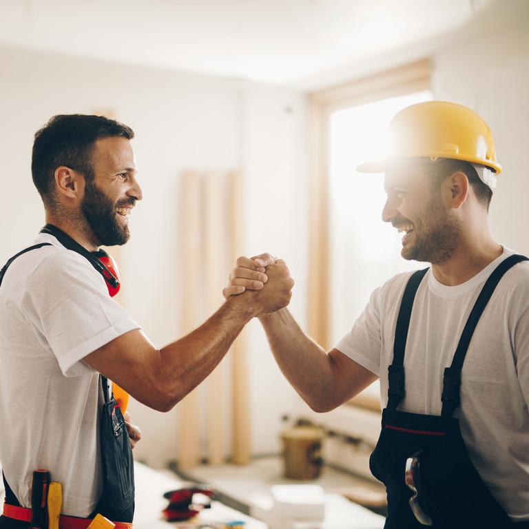 zwei Handwerker begrüßen sich auf einer Baustelle