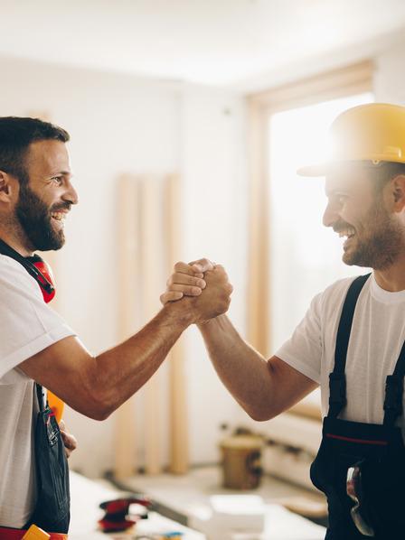 zwei Kollegen reichen sich zur Begrüßung die Hand
