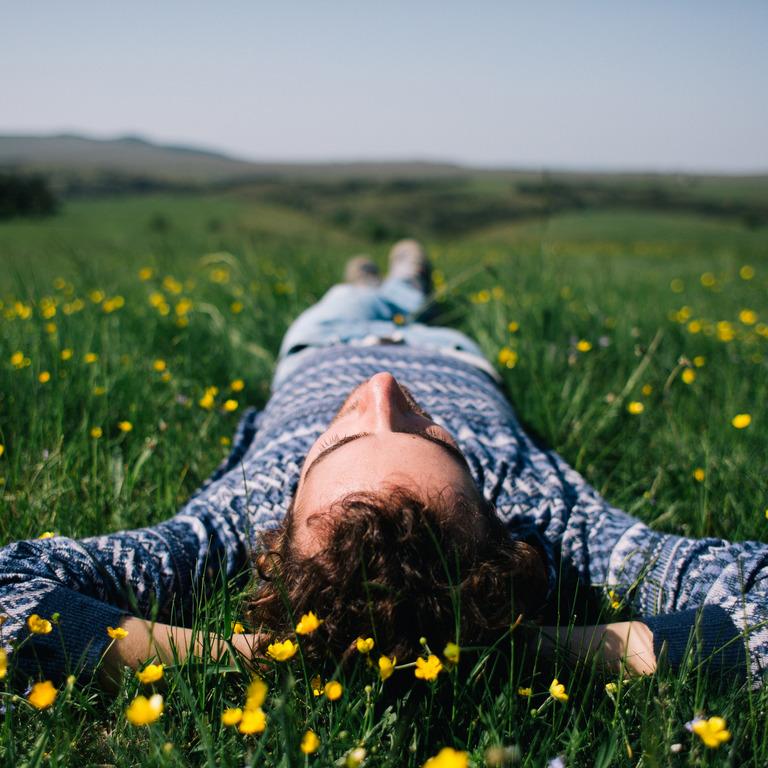 Mann liegt auf einer Blumenwiese und blickt in den Himmel