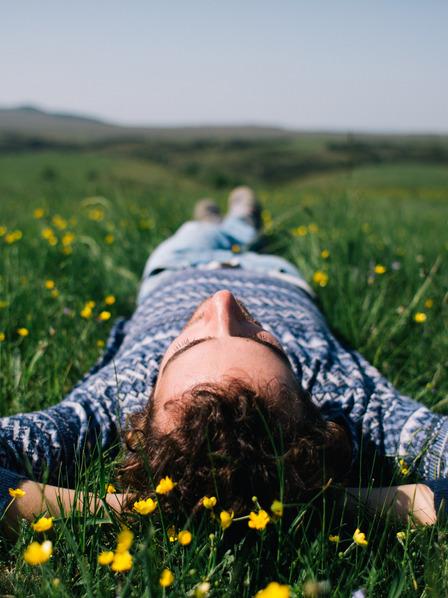 Mann liegt entspannt auf einer Wiese und blickt in den Himmel