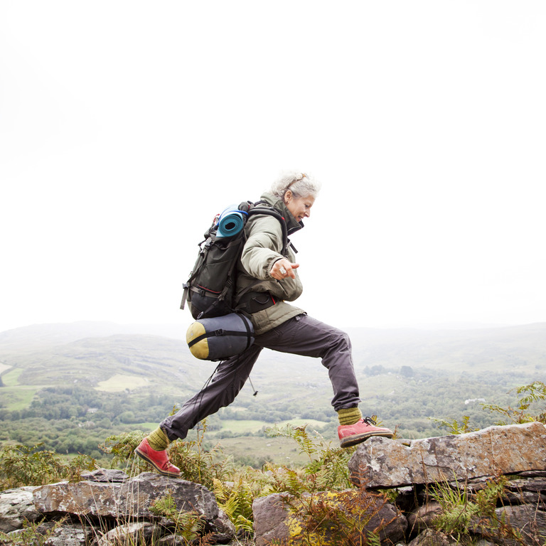 Ältere Frau in Wanderkleidung läuft über einen steinigen Weg