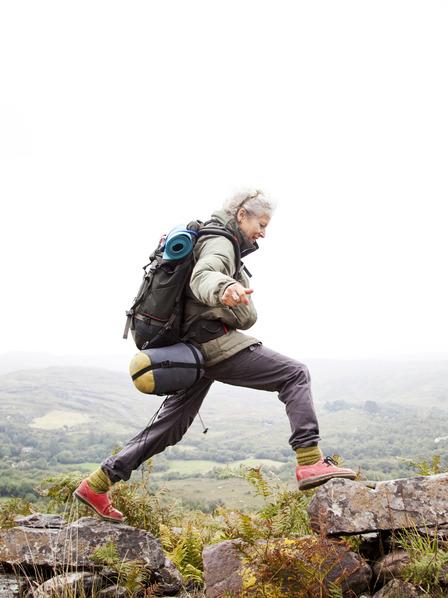 Frau wandert über eine Trockensteinmauer