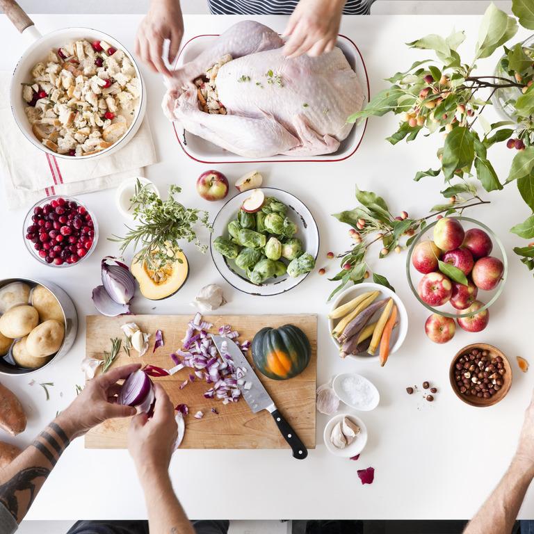 Eine Arbeitsplatte mit vielen gesunden Lebensmitteln, die von drei Händepaaren zubereitet werden.